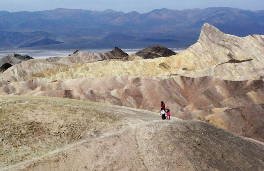 Tourists walk along a ridge at Death Valley National Park, where temperatures could reach 124 this week as a sweltering system envelopes much of the region. Photo: Brian Melley, STF / Copyright 2017 The Associated Press. All rights reserved.