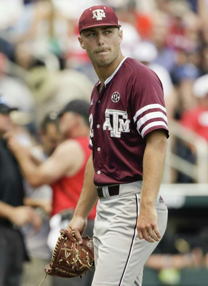 Pitcher Corbin Martin looks back toward the field as he walks to the Texas A&M dugout after being lifted in the second inning. He was charged with five runs allowed after breezing through the first inning.