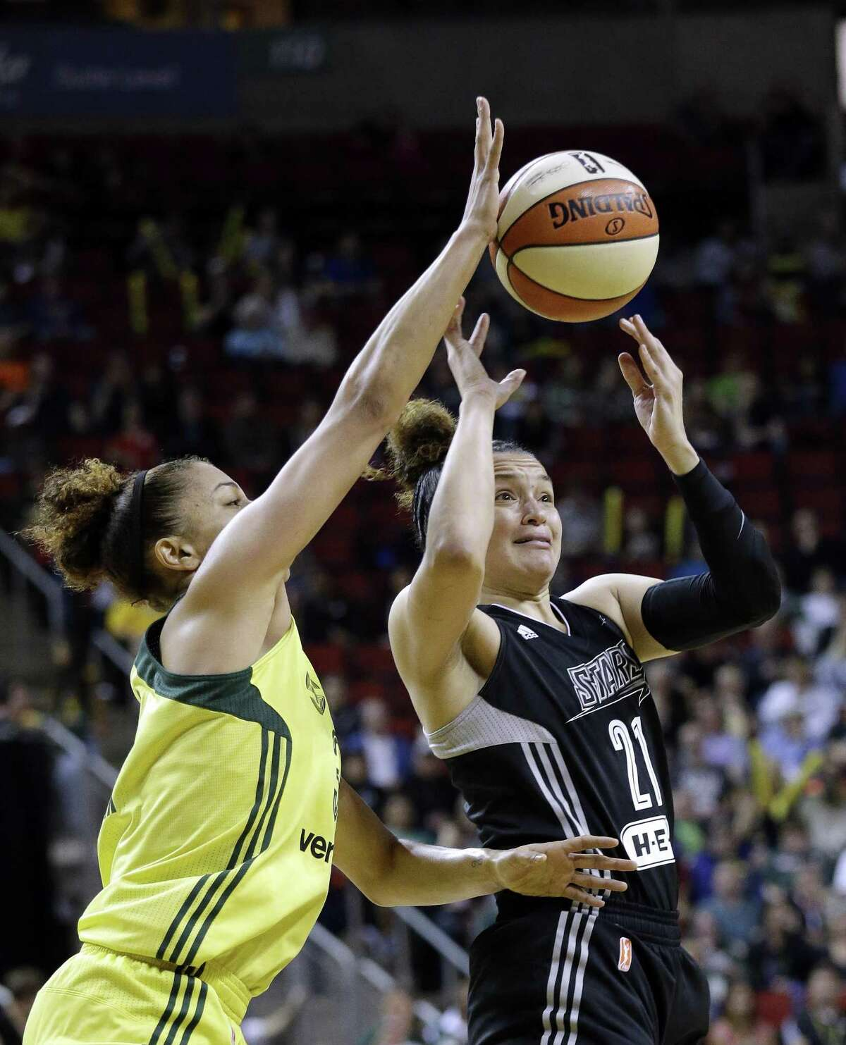 Seattle Storm's Alysha Clark, left, tries to knock the ball away from San Antonio Stars' Kayla McBride in the first half of a WNBA basketball game Sunday, June 18, 2017, in Seattle. (AP Photo/Elaine Thompson)