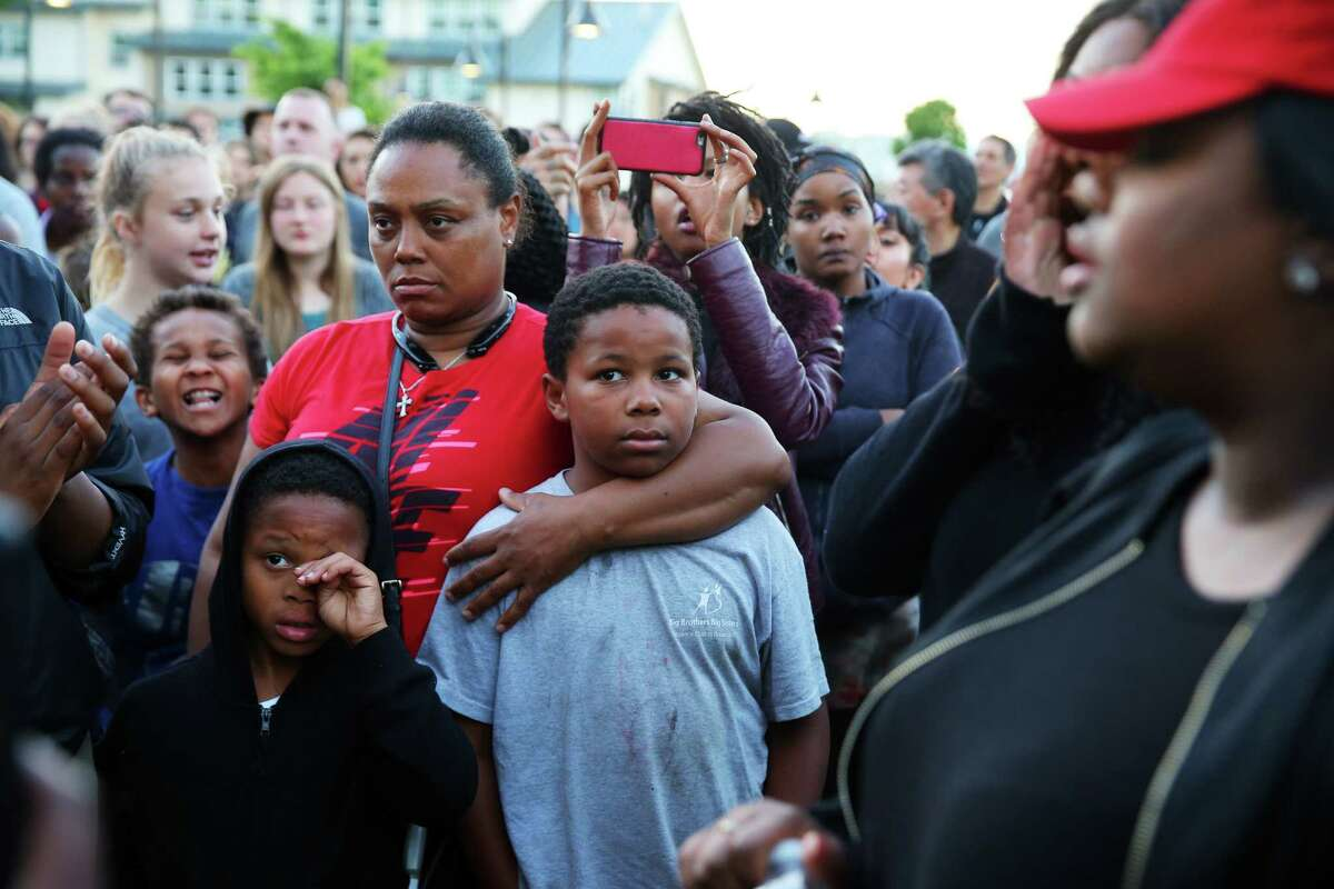 Florida Carroll (in red), a step-sister of Charleena Lyles, stands with several dozen people attending a vigil outside the apartment building of Lyles, a 30-year-old woman who was shot by police after she called them to respond to an attempted burglary, Sunday, June 18, 2017. Lyles has a history of mental illness and police say she brandished a knife during the incident.