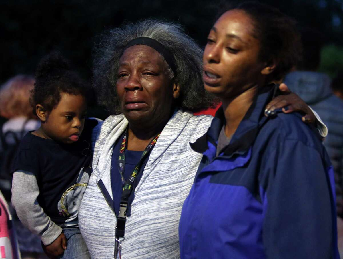 Charleena Lyles's aunt Laurie Davis and oldest sister Monika Williams hold each other as several dozen people attend a vigil outside the apartment building of Charleena Lyles, a 30-year-old woman who was shot by police after she called them to respond to an attempted burglary, Sunday, June 18, 2017. Lyles has a history of mental illness and police say she brandished a knife during the incident.