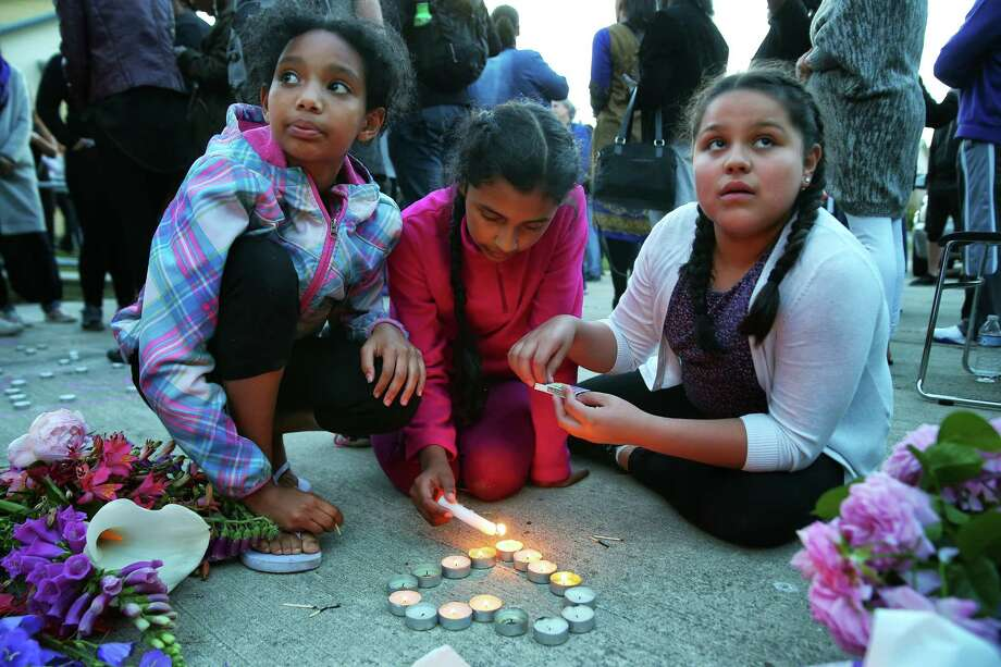 Bethel Tesfay, left, Jocelyn Rojas-Flores, center, and Alondra Luna, all 11-year-olds and residents of the Brettler Family Place apartment complex, light candles as several dozen people attend a vigil outside the apartment building of Charleena Lyles, a 30-year-old woman who was shot by police after she called them to respond to an attempted burglary, Sunday, June 18, 2017. Lyles has a history of mental illness and police say she brandished a knife during the incident. Photo: GENNA MARTIN, SEATTLEPI.COM / SEATTLEPI.COM