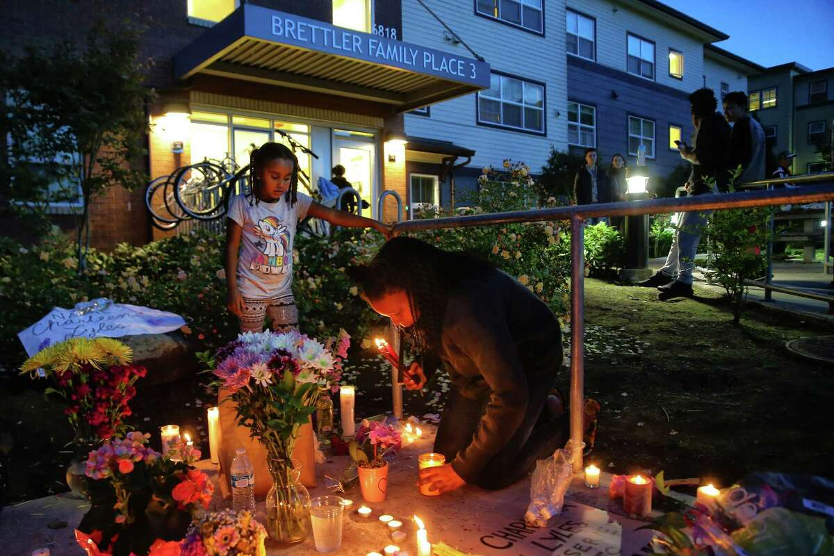 Several dozen people attend a vigil outside the apartment building of Charleena Lyles, a 30-year-old woman who was shot by police after she called them to respond to an attempted burglary, Sunday, June 18, 2017. Lyles has a history of mental illness and police say she brandished a knife during the incident.