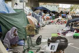 A woman who goes by the name T stays outside a friend's tent near Northgate Avenue and Sycamore Street on Thursday, May 25, 2017, in Oakland, Calif. T was temporarily removed from her tent around the corner as Oakland officials cleared the street for cleaning.