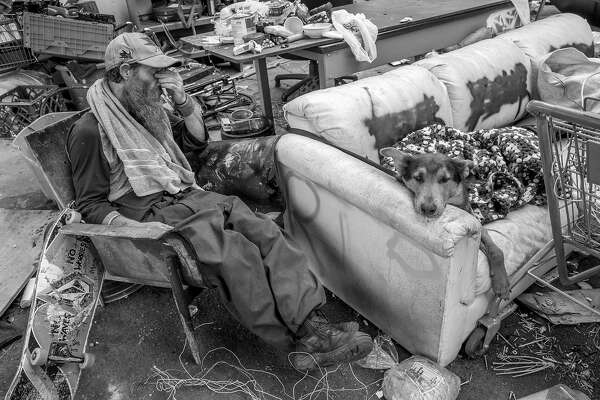 Tom and his dog Winter take a moment as they hang out at his friend's camp site near 5th and Market streets on Tuesday, May 30, 2017, in Oakland, Calif. Tom's camp is across the street.