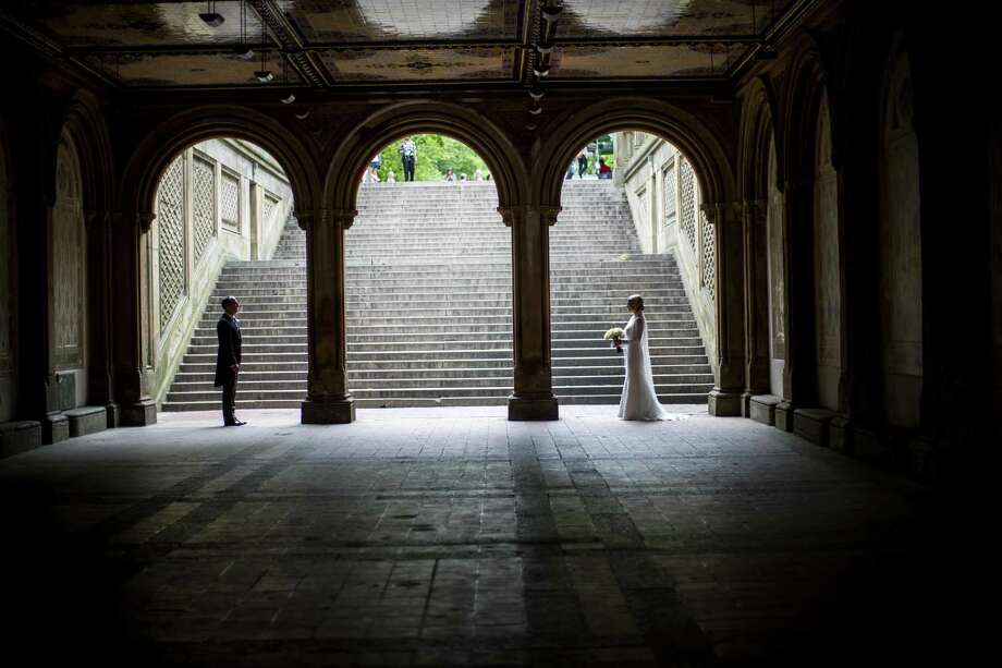 A bride and groom pose for their wedding pictures at the Bethesda Terrace in New York's Central Park, Tuesday, May 23, 2017. According to the Connecticut Better Business Bureau, two to three months is a typical time frame to get wedding pictures to their clients. But, in some cases, couples can get stuck waiting up to a year for photos.  (AP Photo/Mary Altaffer) Photo: Mary Altaffer / Associated Press / Copyright 2017 The Associated Press. All rights reserved.