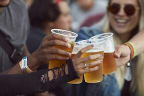 Close-up of hands toasting in beer, at festival