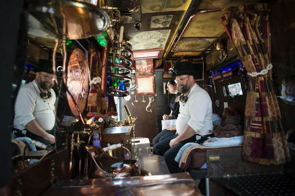 Steampunk enthusiasts sit in their customised motorhome as they attend the first day of 'The Asylum Steampunk Festival' in Lincoln, northern England on August 26, 2016. The four-day alternative lifestyle festival is the largest and longest running steampunk festival in the World; combining art, literature, music, fashion and comedy. Steampunk is a subgenre of science fiction or science fantasy that incorporates technology and aesthetic designs inspired by 19th-century industrial steam-powered machinery.