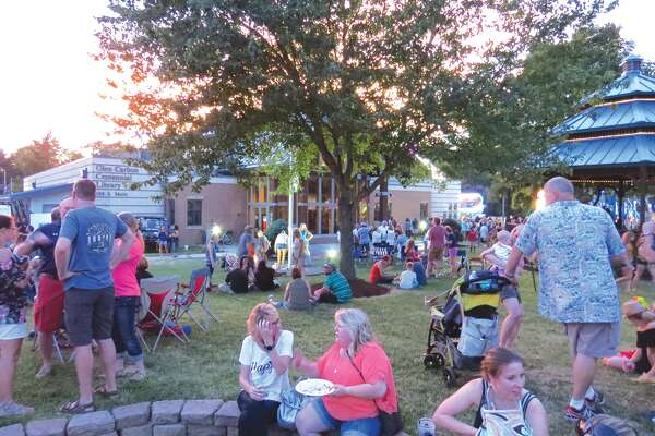 Visitors to the Glen Carbon Homecoming take a break on the lawn in front of the Centennial Library Saturday night. The event featured live music, carnival rides, a parade, fireworks and plenty of food and drinks.