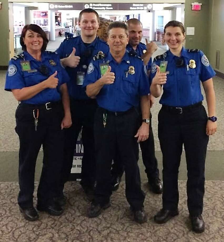 """The checkpoint security crew at Albany International Airport celebrates the recovery of a missing diamond that fell out of a traveler's engagement ring this month. From left, Supervisor Louetta """"Rainy"""" Littman, with officer Steven Kaminski, who found the stone in a checkpoint bin, and fellow officers Andrew Praga, Michael Bouck and Marta Havrylyshyn. Photo: Farbstein, Lisa, Courtesy Of U.S. Transportation Security Administration."""