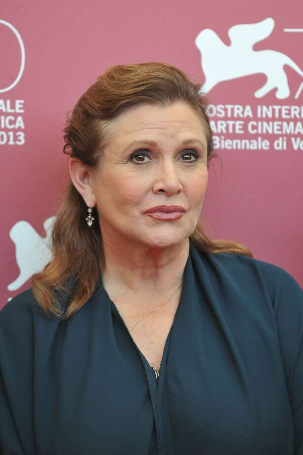 """(FILES) This file photo taken on August 28, 2013 shows US actress and scriptwriter Carrie Fisher posing during a photocall of the jury on the first day of the 70th Venice Film Festival on August 28, 2013 at Venice Lido.  A mixture of drugs including cocaine and ecstasy were in actress Carrie Fisher's system when she suffered a fatal mid-air heart attack, a coroner's report revealed on June 19, 2017. The """"Star Wars"""" actress was rushed to hospital in Los Angeles on December 23, 2016 after collapsing on a flight from London and was pronounced dead four days later. / AFP PHOTO / Tiziana FABITIZIANA FABI/AFP/Getty Images Photo: TIZIANA FABI, AFP/Getty Images"""
