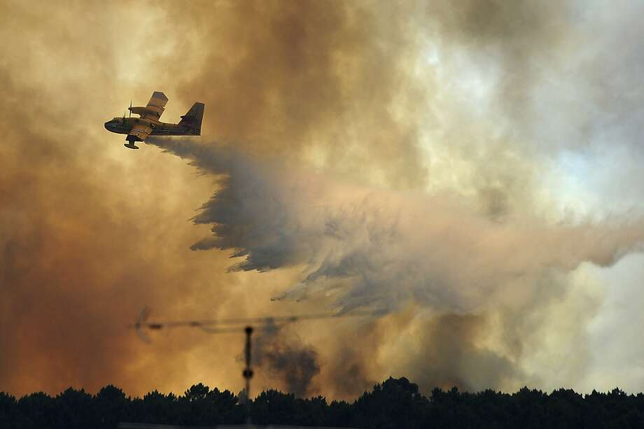 A firefighting aircraft drops water over a blaze burning outside the village of Pedrogao Grande in central Portugal. More than 2,700 firefighters are battling to contain several major wildfires. Photo: Paulo Duarte, Associated Press