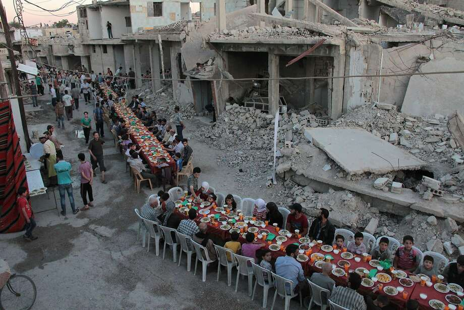 Residents of Douma, Syria, end their daily Ramadan fast and sit for their evening meal. Photo: HAMZA AL-AJWEH, AFP/Getty Images