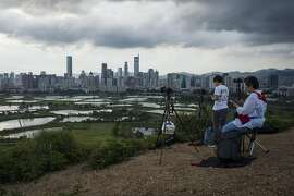 Photographers shoot the Shenzhen - Hong Kong border at dusk in the Ma Tso Lung district of Hong Kong, China, on Thursday, June 8, 2017. Shenzhen is pivoting from its legacy as ground zero for China's manufacturing boom into a center for research, development and production of advanced technology. Photographer: Justin Chin/Bloomberg