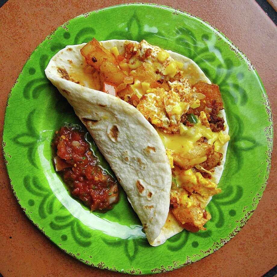 Chorizo Delight taco with chorizo, potatoes, cheese, scrambled eggs and pico de gallo on a handmade flour tortilla Taco Riendo. Photo: Mike Sutter /San Antonio Express-News