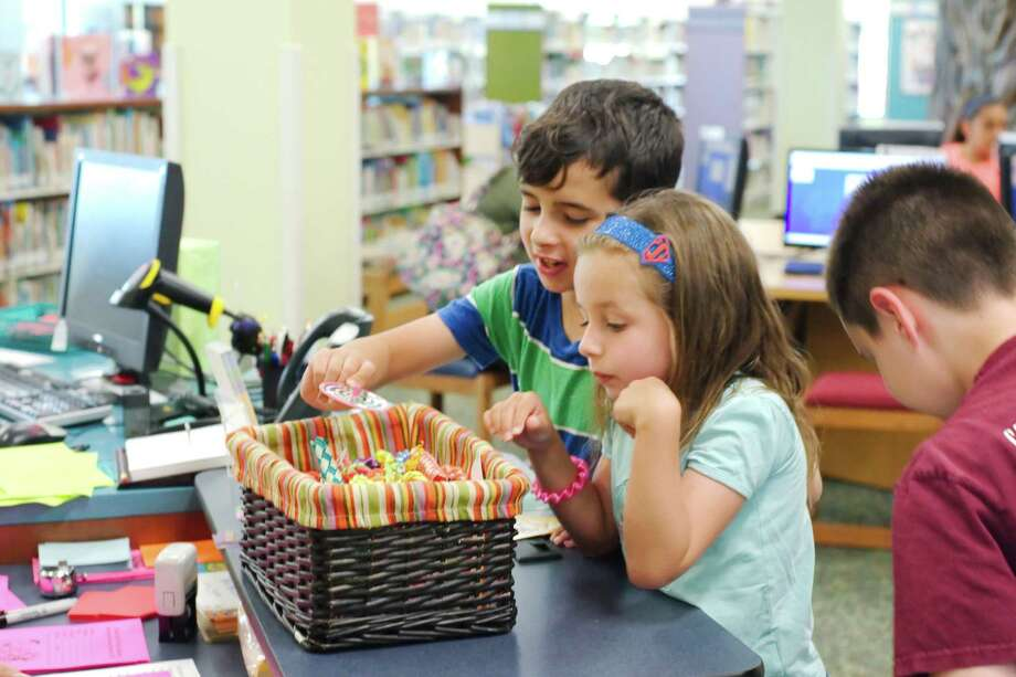 Ayden McDonald and Kyrstin McDonald look over the basket of prizes after turning in their completed summer reading logs at the Deer Park Public Library. Photo: Kirk Sides / © 2017 Kirk Sides / Houston Chronicle