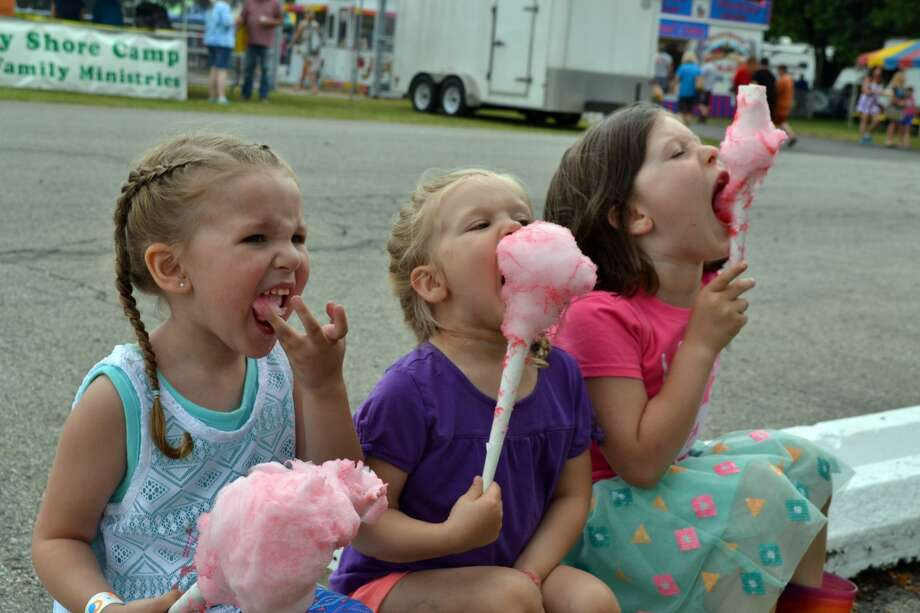 Above, Ellena Nitz, 3, Selah Kuhl, 3, and Bridgette Kuhl, 5, indulge in freshly made cotton candy – the perfect treat for a festival celebrating the Michigan Sugar Festival. Photo: Casey Johnson/For The Tribune