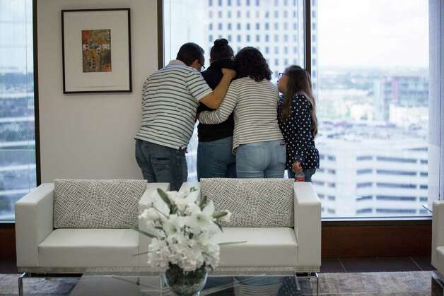 Juan Rodriguez, left, consoles his daughter Rebecca Rodriguez, 15, with the support of his other daughters, Karen Rodriguez, 18, and Kimberly Rodriguez, 10, from the 14th floor of the Two Allen Center (1200 Smith Street), Monday, June 19, 2017, in Houston. Photo: Marie D. De Jesus, Houston Chronicle / © 2017 Houston Chronicle