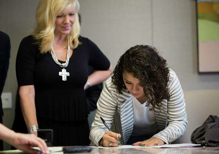 Karen Rodriguez, 18, signs documents witnessed by Kelly Jo Cannon, left, moments before submitting a lawsuit against the federal government, Monday, June 19, 2017, in Houston.