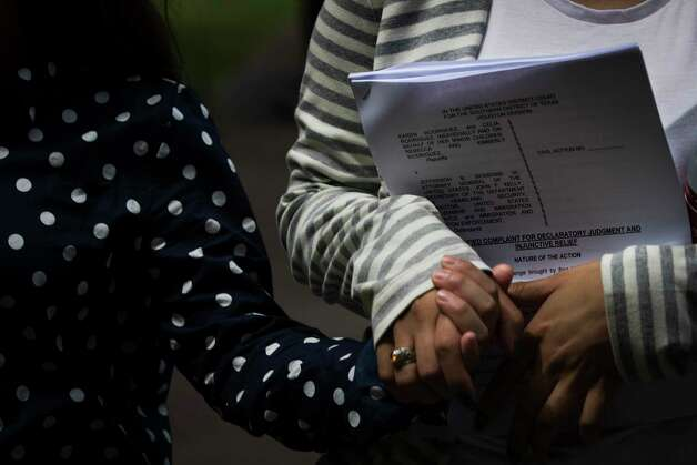 Karen Rodriguez, 18, holds the hand of her younger sister Kimberly Rodriguez, 10, carrying the complaint against the federal government on behalf of the three American daughters and the American wife of Juan Rodriguez who is about to be deported. Monday, June 19, 2017, in Houston. Photo: Marie D. De Jesus, Houston Chronicle / © 2017 Houston Chronicle