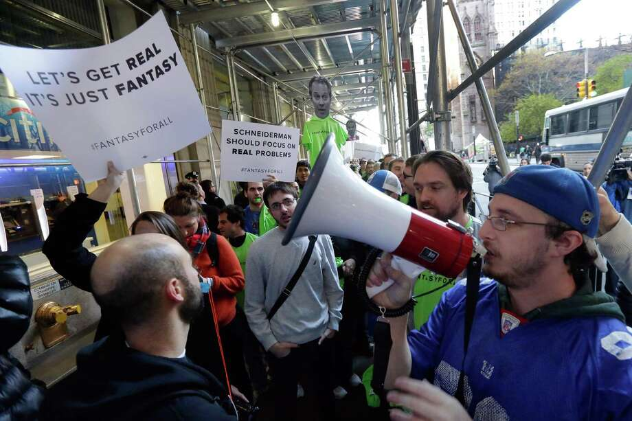 Fantasy sports enthusiasts demonstration in November 2015 in New York City after the state attorney general called daily fantasy sports as gambling operations subject to state regulation. On June 19, 2017, the Federal Trade Commission sued to stop a merger between the two largest DFS operators DraftKings and FanDuel, arguing it would hurt competition in the industry. (AP Photo/Richard Drew) Photo: Richard Drew / Associated Press / AP