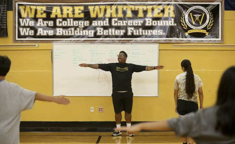 Coach Paris Tyus leads students on a stretching exercise June 19 at Whittier Middle School during the San Antonio Independent School District's Athletic Conditioning & Enrichment pilot program, or ACE. Photo: John Davenport /San Antonio Express-News / ©John Davenport/San Antonio Express-News