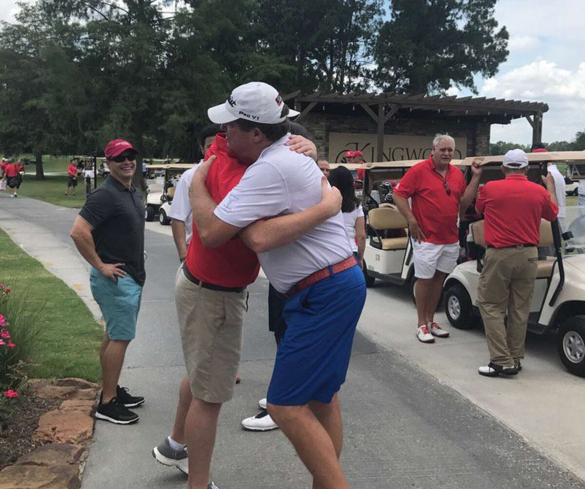 Steve Elkington (right) hugs University of Houston football coach Major Applewhite at Monday's golf tournament at Kingwood Country Club.
