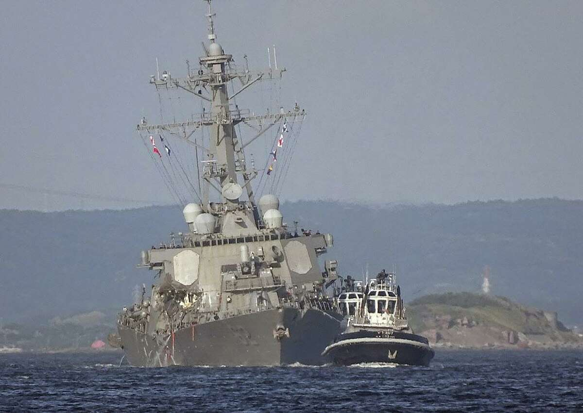 In this Saturday, June 17, 2017 file photo, the damaged USS Fitzgerald is towed by a tugboat in the waters near the U.S. Naval base in Yokosuka, southwest of Tokyo, after the U.S. destroyer collided with the Philippine-registered container ship ACX Crystal in the waters off the Izu Peninsula. (AP Photo/Eugene Hoshiko, File)