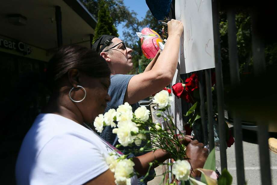 Barbara Branch arranges flowers and Drew Wehrstein writes a message at the makeshift memorial in Diamond Heights for slain UPS driver Mike Lefiti . Photo: Elijah Nouvelage, Special To The Chronicle