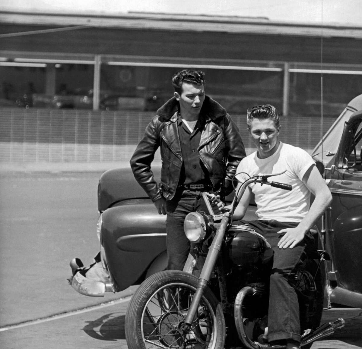 Grease is the word! Two teens hang out on their motorcycle and car during the 1950s.
