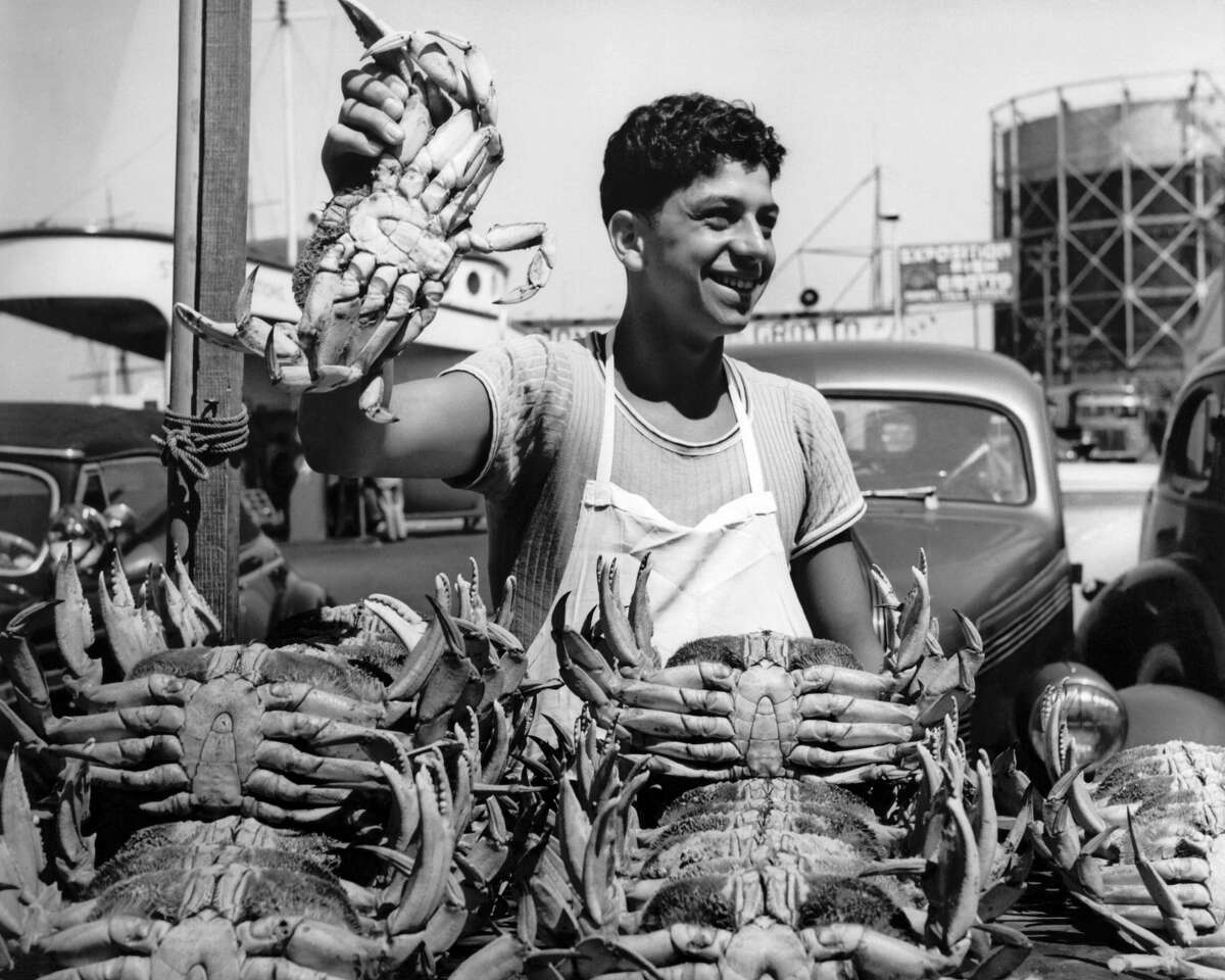 A happy worker at Fisherman's Wharf holds up a crab from a large pile of fresh-caught Dungeness crabs on April 16, 1945.