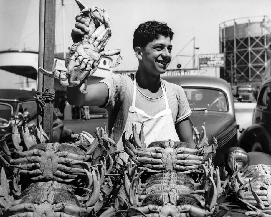 A happy worker at Fisherman's Wharf holds up a crab from a large pile of fresh-caught Dungeness crabs on April 16, 1945. Photo: Underwood Archives/Getty Images
