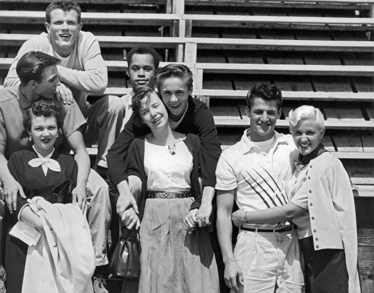A group of teenage boys and girls having fun for the camera in 1955.