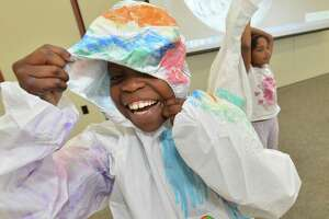 Marlinn Alphonse gets to try on his spacesuit after he created his own design with others on the first day of the 'Blast-Off Camp!' on Monday at the Norwalk Public Library.