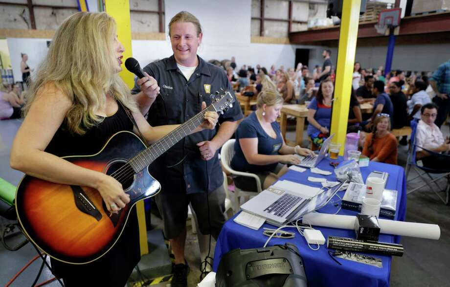 """Wendy Jones sings """"Smelly Cat"""" as emcee Eric Allen holds the mic as """"Friends"""" trivia night kicks off to a full house at Eureka Heights Brewery in Houston, TX, June 14, 2017. (Michael Wyke / For the  Chronicle) Photo: Michael Wyke, Freelance / © 2017 Houston Chronicle"""