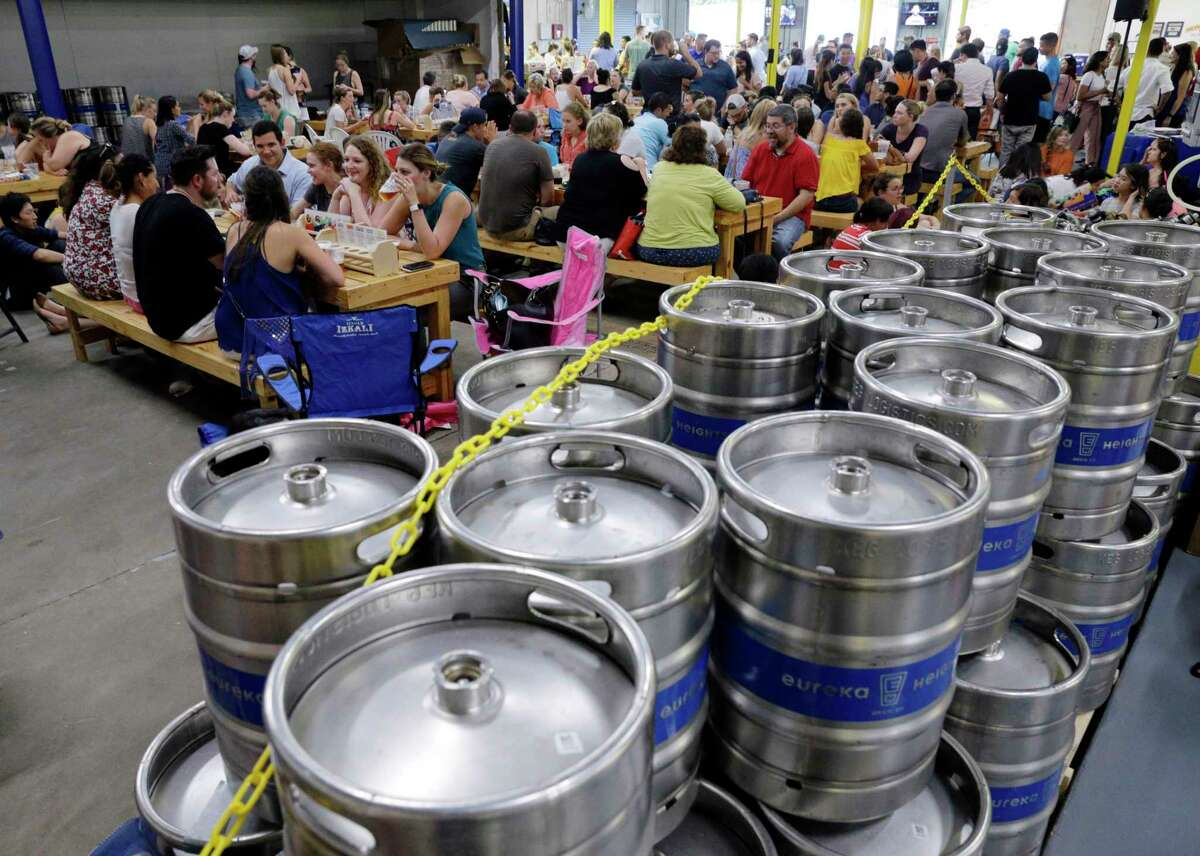Tables are packed next to rows of kegs during