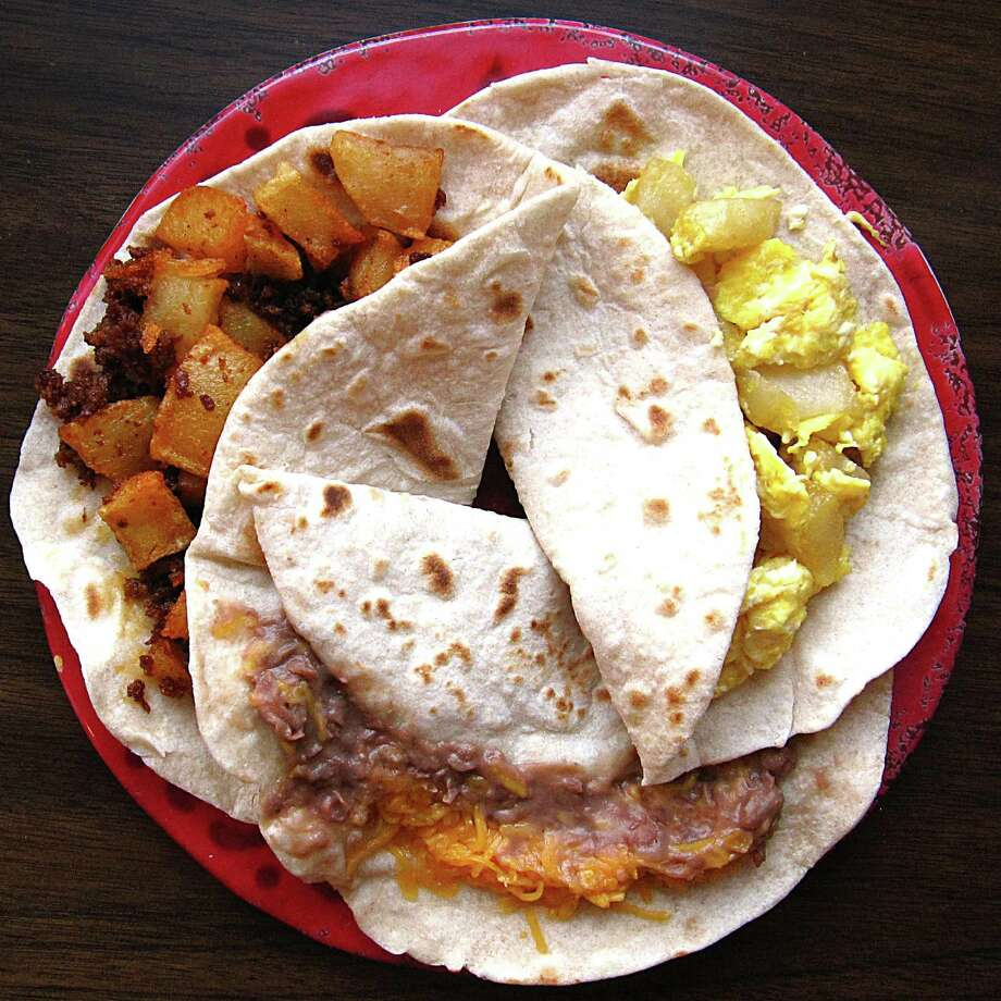 Three breakfast tacos for $2.50. From top left: chorizo and potato, egg and potato, bean and cheese, all on handmade flour tortillas, from Luchis Mexican Restaurant. Photo: Mike Sutter /San Antonio Express-News