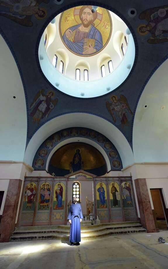 Rev. Harry Pappas, presiding priest of Archangels Greek Orthodox Church is bath in light as he stands in the sanctuary of the 1954 church building that is undergoing a $2 million renovation in Stamford, Conn., on Wednesday, June 14, 2017. The plan is to renovate the church in time to reopen in September or October and then remodel the fellowship hall of the church. Photo: Matthew Brown / Hearst Connecticut Media / Stamford Advocate