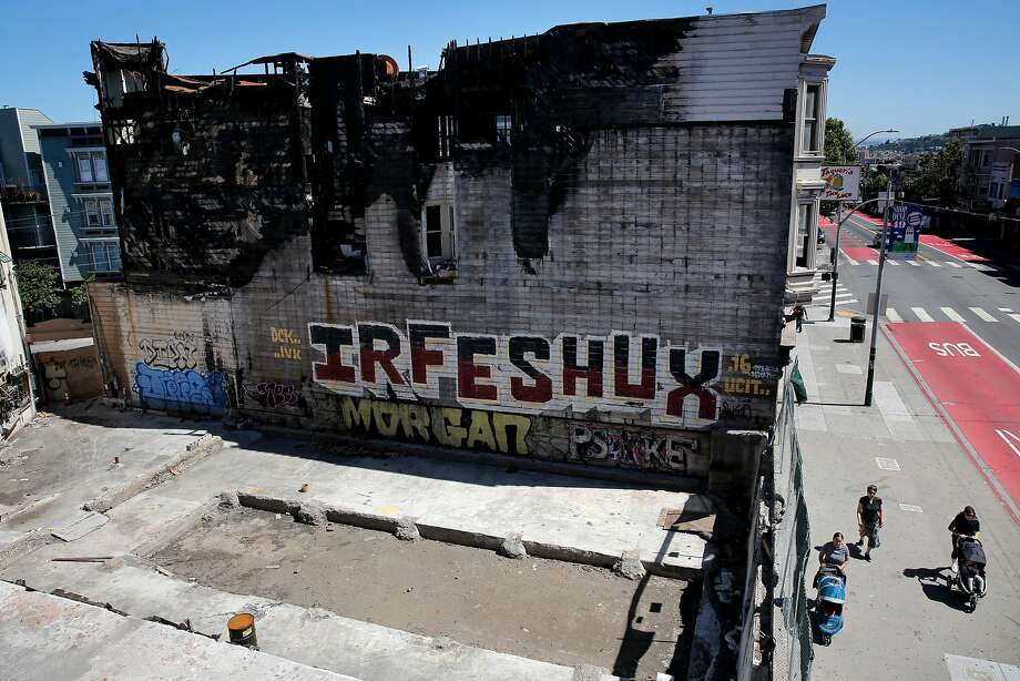 A gaping hole and charred structure remains at the former site of Cole Hardware on Mission Street where a fire a year ago displaced eight businesses and 50 people. Rebuilding has been a slow process with outcomes still uncertain. Photo: Michael Macor, The Chronicle