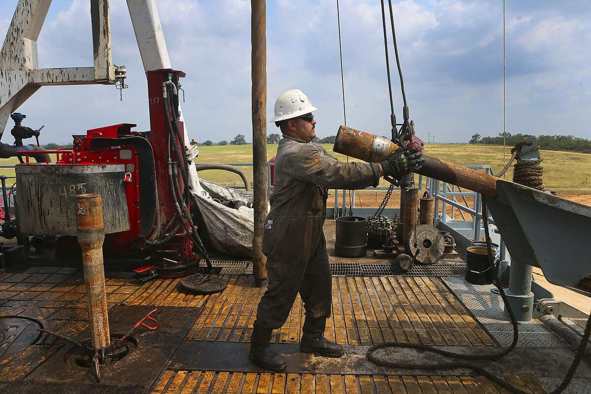Roughneck Eluid (cq) Cervantes pulls up a section of drilling pipe with the help of machinery Thursday May 11, 2017 at the Abraxus Petroleum Shut Eye Unit oil drilling rig in the Eagle Ford Shale in Atascosa County, Texas.