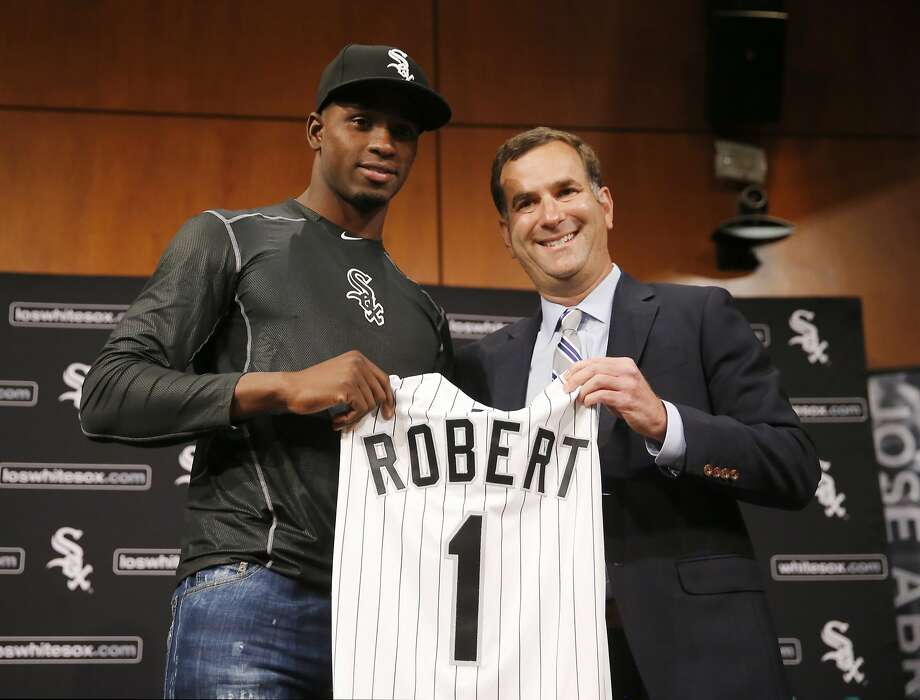 The days when Cuban outfielder Luis Robert (left), shown with White Sox general manager Rick Hahn last month, gets a $26 million signing bonus may have passed. Photo: Charles Rex Arbogast, Associated Press