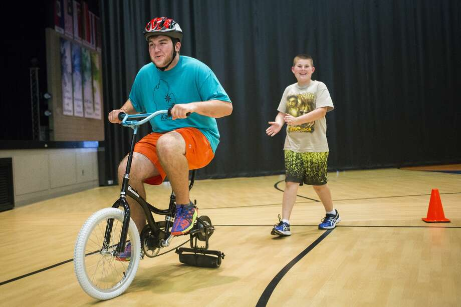 Russell Pitt of Midland, left, rides a modified bike around a track as Adam Jammer of Midland, 12, right, follows behind him during the iCan Bike Camp hosted by The Arc of Midland on Monday, June 19, 2017 at Midland Evangelical Free Church. The iCan Bike roller equipment was designed to help youths with disabilities learn how to ride a bike. The camp continues through Friday, June 23, 2017. Photo: Katy Kildee