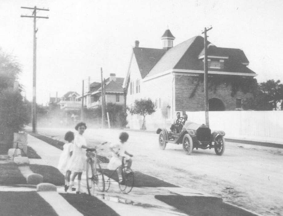 Children wait on the sidewalk with their bicycles while a car travels down Belknap Street in Monte Vista in this undated photo. Photo: Courtesy UTSA Special Collections / UTSA Special Collections