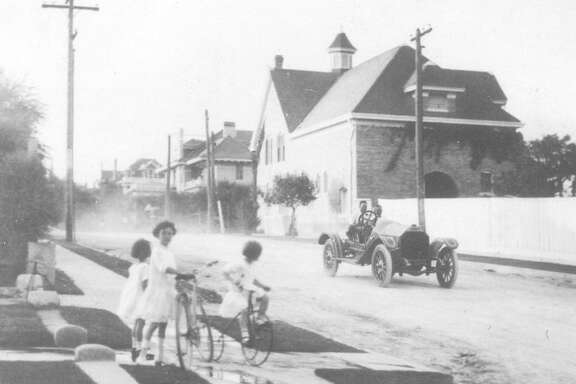 Children wait on the sidewalk with their bicycles while a car travels down Belknap Street in Monte Vista in this undated photo.