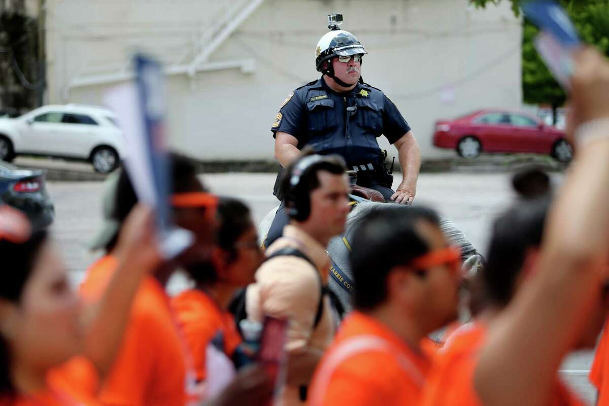 A Houston Police Department officer watches undocumented immigrant youth leaders, students and supporters duing a 2016 march in downtown Houston. (Gary Coronado / Houston Chronicle )