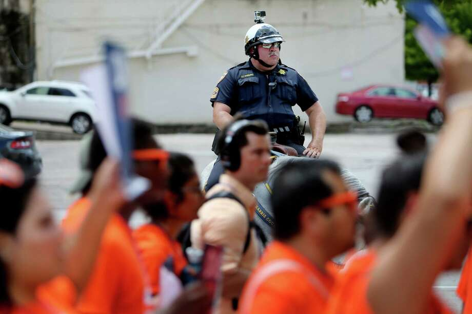A Houston Police Department officer watches undocumented immigrant youth leaders, students and supporters duing a 2016 march in downtown Houston. (Gary Coronado / Houston Chronicle ) Photo: Gary Coronado, Staff / © 2015 Houston Chronicle