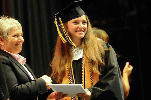 Gaby Baum, right, receives her diploma during the Academy of Information Technology and Engineering (AITE) graduation inside the Rippowam Middle School auditorium in Stamford, Conn. on Monday, June 19, 2017.