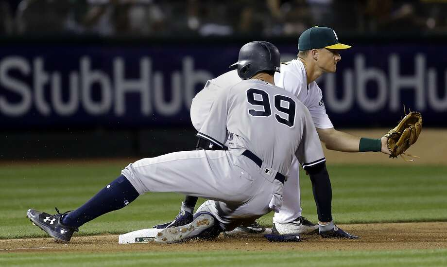New York Yankees' Aaron Judge (99) slides safely past Oakland Athletics' Matt Chapman with a triple during the seventh inning of a baseball game Friday, June 16, 2017, in Oakland, Calif. (AP Photo/Ben Margot) Photo: Ben Margot, Associated Press