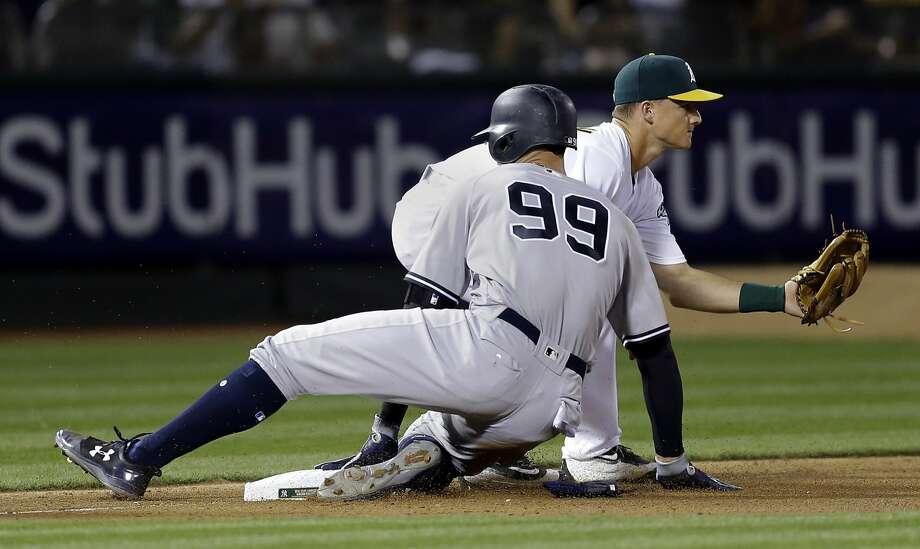 New York Yankees' Aaron Judge (99) slides safely past Oakland Athletics' Matt Chapman with a triple during the seventh inning of a baseball game Friday, June 16, 2017, in Oakland, Calif. (AP Photo/Ben Margot) Photo: Ben Margot, Associated Press