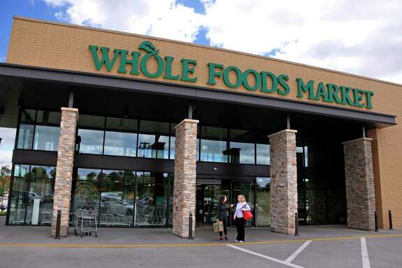 In this May 3, 2017, photo, people stand outside a Whole Foods Market in Upper Saint Clair, Pa. Amazon's planned $13.7 billion acquisition of Whole Foods signals a massive bet that people will opt more for the convenience of online orders and delivery or in-store pickup, putting even more pressure on the already highly competitive industry. (AP Photo/Gene J. Puskar)